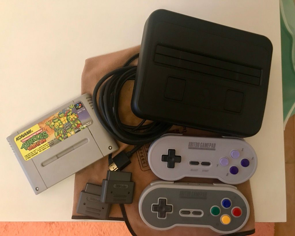 Image shows the SuperNT game console, two controllers, and a japanese Turtles In Time game cart.
